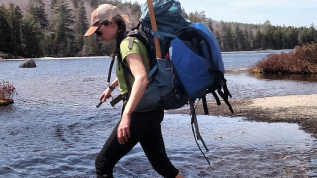 Photo of student researcher stepping over lake rocks.